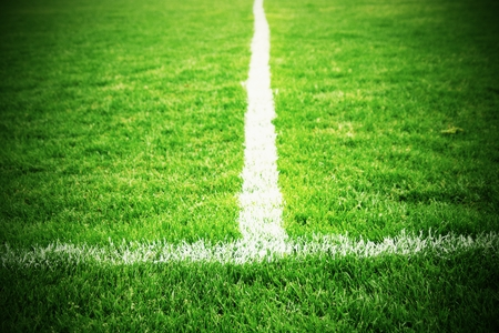 white lines: Cross of painted white lines on natural football grass. Artificial green turf texture.
