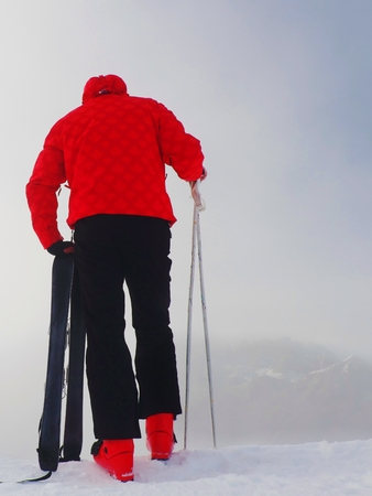 off piste: Skier in red winter jacket with  small fun skis stay in snow in mountains. Fogy winter day at peak. Stock Photo