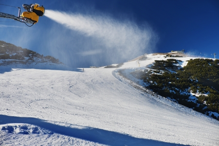 heli: Snowmaking on slope. Skier near a snow cannon making fresch powder snow. Mountain ski resort and winter calm mountain landscape.