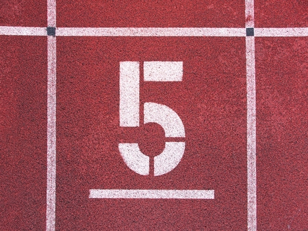 number five: Number five. Big white track number on red rubber racetrack. Gentle textured running racetracks in small athletic stadium. Stock Photo
