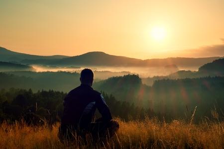en cuclillas: Caminante en la posición en cuclillas en la alta hierba de prado disfrutar del paisaje colorido amanecer Foto de archivo
