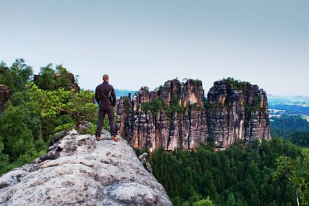 tall man: Tall man in black on cliff and watch to mountains. Dark silhouette of rocks. Stock Photo