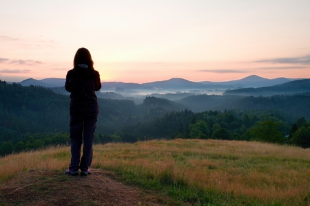 early morning: Long hair woman stand on meadow with golden stalks of grass and watch over misty and foggy morning valley to sunrise