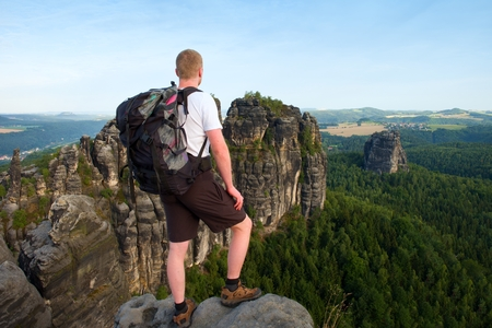 limber: Tall tourist with big backpack. Sunny evening in rocky mountains of Saxony Switzerland park. Hiker stand on rocky view point above valley. Stock Photo