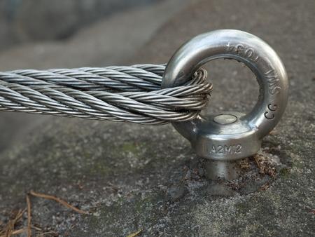 砂岩の岩鋼ボルト アンカー目のディテール。ワイヤー ロープの端のノットです。ヴィア フェラータ登山者パス。鉄は、ブロックの固定ロープをツ