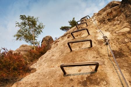 登山のはしご。鉄ネジ スナップ フックでブロックの固定ロープのツイスト。ロープの端は、砂岩の岩に固定されています。 写真素材