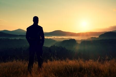 키 등산객 잔디의 황금 줄기 초원에 서서 일출에 안개 낀 안개 낀 아침 계곡 지켜