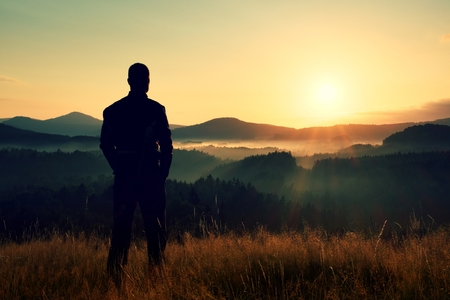Tall hiker stand on meadow with golden stalks of grass and watch over misty and foggy morning valley to sunrise Standard-Bild