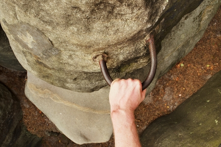 handhold: Rock climbers hands on steel handhold anchored in sandstone rock.
