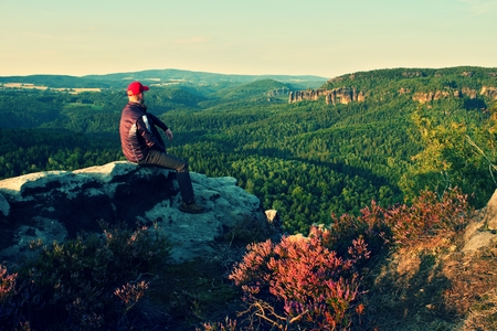 tall man: Tall man in black with red baseball cap on sharp  cliff and watch to valley. Colorful summer morning in park.