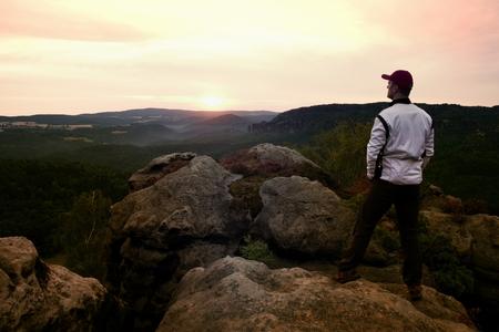 rocky peak: Sportsman in white jacket on rocky peak. Dreamy fogy landscape, beautiful valley below Stock Photo