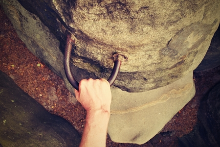 rappel: Rock climbers hands on handhold steel anchored in sandstone rock.