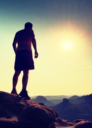 pantalones abajo: turismo delgada en pantalones en el acantilado de roca imperio está mirando hacia abajo al valle de la mañana. Sun caliente por encima.