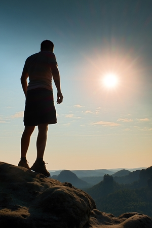pantalones abajo: Slim tourist in pants on the cliff of rock empire is watching down to morning valley. Hot Sun above.