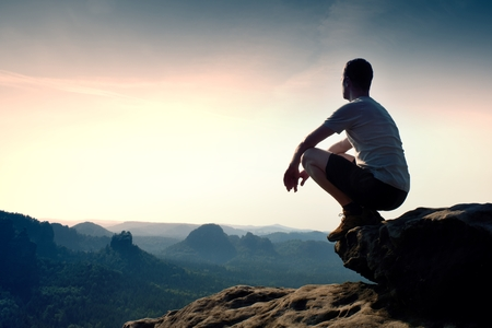 Jonge wandelaar in zwarte broek en shirt zit op de rand van klif en op zoek naar heuvelachtige vallei blaten mistig Stockfoto