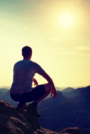 black pants: Young hiker in black pants and shirt  is sitting on cliffs edge and looking to misty hilly valley bellow