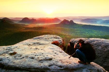 崖と思考に三脚とプロの写真家。美しい渓谷の下で夢のような濃霧発生風景、青い霧日の出 写真素材