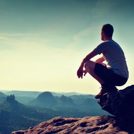 黒のズボンとシャツに若いハイカーは崖の端に座って、霧の丘陵の谷の下まで探して