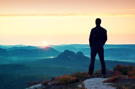 Hiker in sportswear stand on the peak of sandstone rock in rock empires park and watching over the misty and foggy morning valley to Sun. Beautiful moment the miracle of nature Standard-Bild