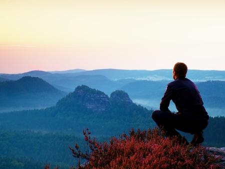 Wandelaar in zwart in gehurkte positie op een klif in heide struiken, genieten van het landschap