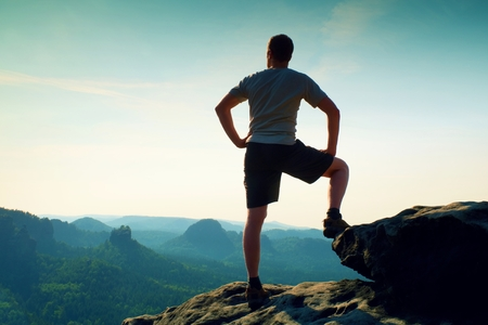 naked black men: Hiker is standing on the peak of sandstone rock in rock empires park and watching over the misty and foggy morning valley to Sun. Beautiful moment the miracle of nature