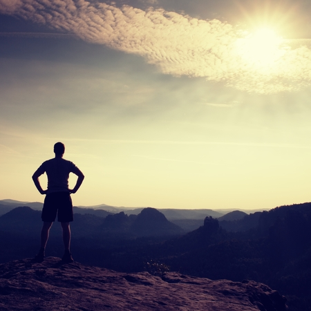 empires: Happy hiker is standing on the peak of sandstone rock in rock empires park and watching over the misty and foggy morning valley to Sun. Stock Photo