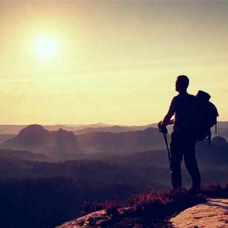 backpack: mochilero alto con postes en la mano. Soleado de primavera del amanecer en las montañas rocosas. Caminante con mochila grande de pie en la rocosa punta de visión por encima del valle brumoso.
