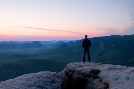 empires: Hiker stand on the sharp corner of sandstone rock in rock empires park and watching over the misty and foggy morning valley to Sun Stock Photo