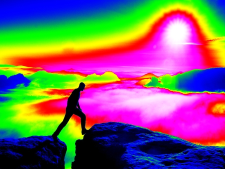 thermogram: Fantastic infrared scan. Tired tourist in black on the rocky peak. Wonderful daybreak in mountains, heavy orange mist in deep valle