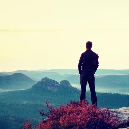 red man: Hombre alto en negro en el acantilado con el arbusto brezo. Sharp Park monta�as rocosas y vistas al punto por encima del valle. Foto de archivo