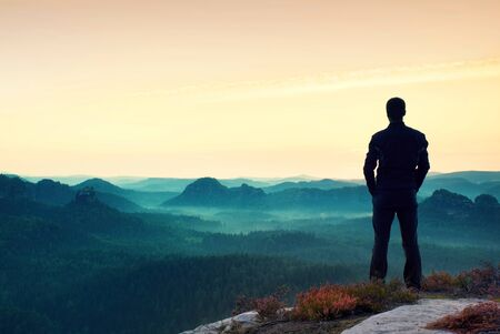 satisfy: Gesture of triumph. Satisfy hiker in grey shirt and dark trousers. Tall man on the peak of cliff watching down to landscape.