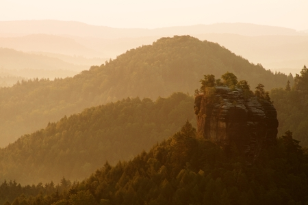 increased: Sunrise in a beautiful mountain of Czech-Saxony Switzerland. Increased sandstone peaks from foggy background, with orange fog