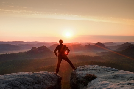 Jumping hiker in black celebrate triumph between two rocky peaks. Wonderful daybreak.