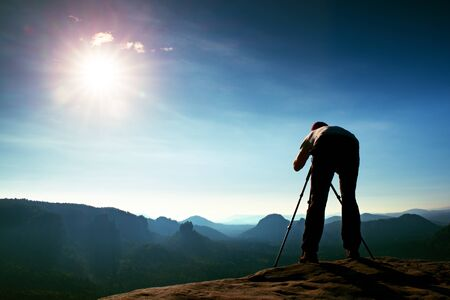 valley below: Professional photographer with tripod on cliff and thinking. Dreamy fogy landscape, blue misty sunrise in a beautiful valley below