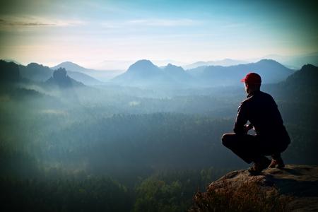 en cuclillas: Corredor en la tapa de color rojo y en ropa deportiva oscura en la posici�n en cuclillas sobre una roca, disfrutar del paisaje Foto de archivo