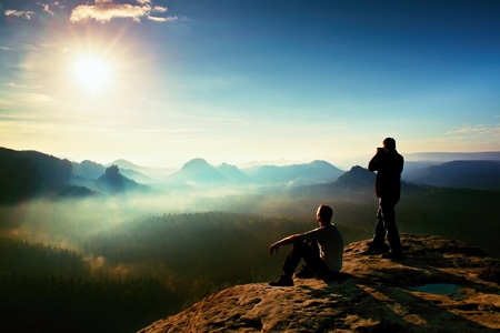 Hiker and photo enthusiast stay with tripod on cliff and thinking. Dreamy fogy landscape, blue misty sunrise in a beautiful valley below Standard-Bild