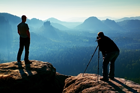 documenting: Hiker and photo enthusiast stay with tripod on cliff and thinking. Dreamy fogy landscape, blue misty sunrise in a beautiful valley below Stock Photo