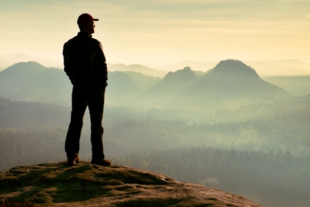 strip shirt: Alone hiker in red cap stand on the peak of sandstone rock in rock empires park and watch into sun Stock Photo