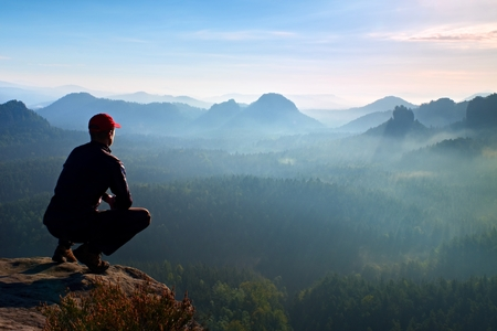 squatting: Runner in red cap and  in dark sportswear in squatting position on a rock, enjoy the scenery Stock Photo