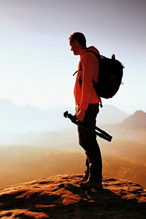 hobbyist: Silhouette of photographer overlooking a blanket of fog over valley to sun