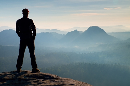 empires: Hiker is standing on the peak of sandstone rock in rock empires park and watching over the misty and foggy morning Stock Photo