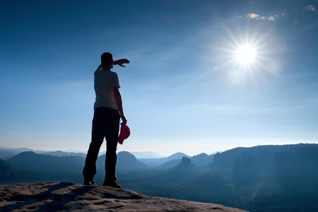 empires: Hiker in red cap on peak of rock in rock empires park and watching over the misty and foggy morning valley to Sun. Beautiful moment the miracle of nature