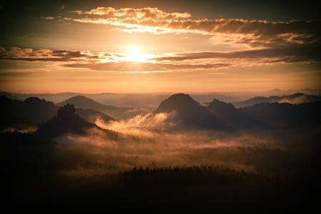 marvelous: Heavy misty daybreak. Misty sunrise in a marvelous hilly Saxony Switzerland  park . Peaks of hills are sticking out from dense orange  fog.