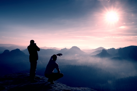 valley below: Hiker and photo enthusiast stay on cliff and thinking. Dreamy fogy landscape, blue misty sunrise in a beautiful valley below
