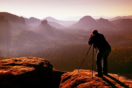 Professional on cliff. Nature photographer takes photos with mirror camera on peak of rock. Dreamy fogy landscape, spring orange pink misty sunrise in a beautiful valley below.