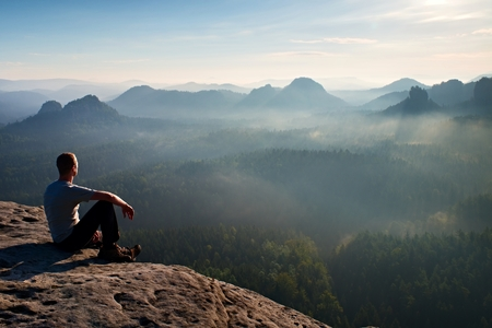 Tall short hair hiker in shirt sit on a rock and enjoy foggy  scenery