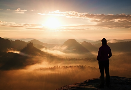 Alone young girl tourist feast daybreak on the sharp corner of sandstone rock and watch over valley to Sun. Archivio Fotografico