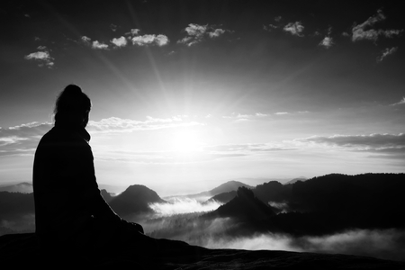 profile silhouette: Beautiful  young woman tourist enjoy daybreak on the sharp corner of sandstone rock and watch over valley to Sun.