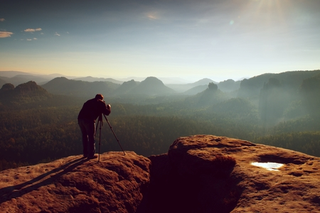 mountain valley: Professional on cliff. Nature photographer takes photos with mirror camera on peak of rock. Dreamy fogy landscape, spring orange pink misty sunrise in a beautiful valley below.