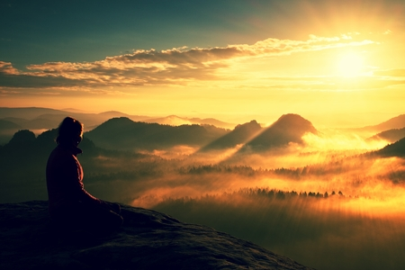 wonderful: Beautiful  young woman tourist enjoy daybreak on the sharp corner of sandstone rock and watch over valley to Sun.